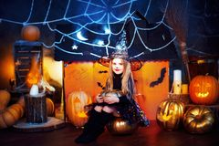 Happy Halloween. A little beautiful girl in a witch costume celebrates with pumpkins royalty free stock image