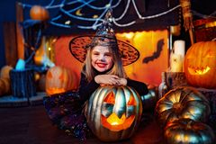 Happy Halloween. A little beautiful girl in a witch costume celebrates with pumpkins stock photos