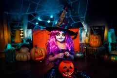 Happy Halloween. A little beautiful girl in a witch costume celebrates with pumpkins royalty free stock photo