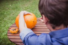 Happy halloween. Man carving big pumpkin Jack O Lanterns for Halloween outside. Close-up stock photo