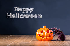 Happy Halloween message with pumpkin and spider. On black background Stock Images