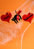 Happy Halloween message written across red hearts and black cat with pegs hanging from a line - vertical with copy space. Royalty Free Stock Photos