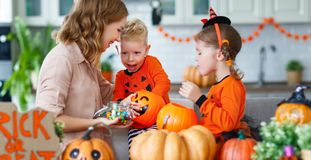 Happy Halloween! mother treats children with candy at home royalty free stock photography