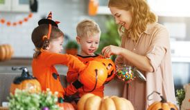 Happy Halloween! mother treats children with candy at home royalty free stock photos