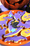 Happy Halloween orange and purple sugar cookies in cat, hat, bat and pumpkin shapes - vertical closeup. Royalty Free Stock Photography