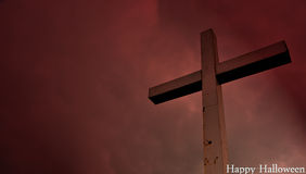 Happy halloween postcard: Cross situated on a hill in dramatic clouds Stock Images