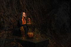 Happy Halloween! A pretty witch with a big pumpkin. Beautiful yo stock photo