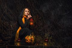 Happy Halloween! A pretty witch with a big pumpkin. Beautiful yo Royalty Free Stock Images