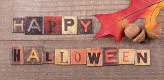 Happy Halloween Sign. With oak leaf and acorns on a wood surface Royalty Free Stock Images