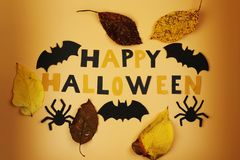 A happy halloween sign with some black bats and spiders. Trick or treating. American holiday. A autumn leaves. Orange and black. S. A happy halloween sign with stock images