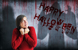 Happy Halloween sprayed on wall next to scared woman Royalty Free Stock Image