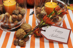 Happy Halloween table centerpiece. Happy Halloween tag message with orange candles and nuts centerpieces with pumpkin jack o lantern decorations Royalty Free Stock Images