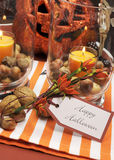 Happy Halloween table centerpiece. Vertical. Happy Halloween tag message with orange candles and nuts centerpieces with pumpkin jack o lantern decorations Stock Photo