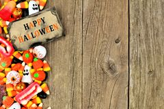 Happy Halloween tag with candy side border over rustic wood Royalty Free Stock Photo