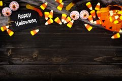 Happy Halloween tag with candy top border on black wood Royalty Free Stock Images