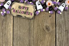 Happy Halloween tag with candy top border over aged wood Royalty Free Stock Image