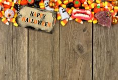 Happy Halloween tag with candy top border over rustic wood Royalty Free Stock Image