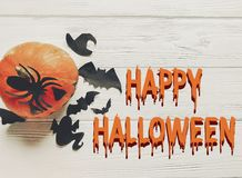 Happy halloween text flat lay. jack lantern pumpkin with witch g. Host bats and spider black decorations on white wooden background top view, space for text Royalty Free Stock Photo