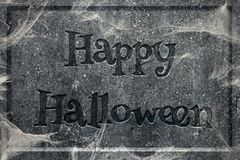 Happy Halloween tombstone. Tombstone with engraved words Happy Halloween covered in cobwebs Stock Images