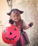 Happy Halloween Trick or Treat Girl at Door. A little girl is dressed up in a pink pirate costume trick or treating at a door with a pumpkin basket and smiling stock images