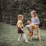 Happy Halloween. Two sisters play with little pumpkin Jack O Lanterns outdoors. Vintage filter effect royalty free stock photo