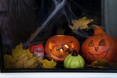 Happy halloween The window of a house decorated for the holiday. Pumpkins, web, candles and autumn leaves Royalty Free Stock Images