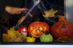 Happy halloween The window of a house decorated for the holiday. Pumpkins, web, candles, hend with blood and autumn leaves on a window Stock Images