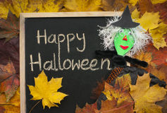 Happy Halloween, witch, autumn. Happy Halloween. Message in chalk writing on a black school board on autumn leaves background. Witch puppet made of wooden spoon royalty free stock image