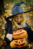 Happy halloween witch girl keeps pumpkin Royalty Free Stock Images