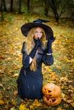 Happy halloween witch girl keeps pumpkin Stock Image