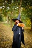 Happy halloween witch girl keeps pumpkin Royalty Free Stock Photo