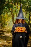 Happy halloween witch girl keeps pumpkin Stock Photo