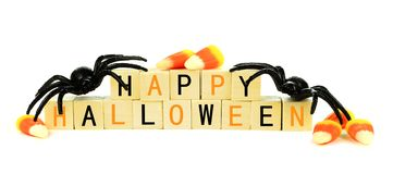Happy Halloween wooden blocks with candy and decor over white. Happy Halloween wooden blocks with toy spider and candy corn isolated on a white background Royalty Free Stock Photo