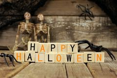 Happy Halloween wooden blocks with decor over old wood background Stock Photos