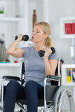 Happy handicapped person on wheelchair with dumbbell. Happy handicapped person on a wheelchair with a dumbbell Royalty Free Stock Image