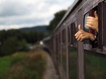 Happy hands on a train. Happy train travellers sticking their thumbs up Stock Images
