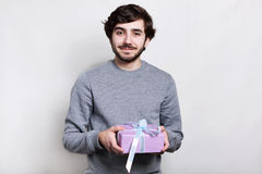 Happy handsome  bearded guy in grey sweater holding  gift and smiling to camera on white background. Holidays time, making surpris Stock Photography