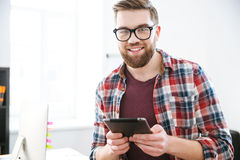 Happy handsome bearded male in glasses using tablet Stock Image