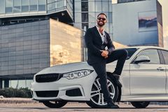 Happy handsome bearded male in sunglasses dressed in a black suit sitting on luxury car against a skyscraper. Happy handsome bearded male in sunglasses dressed Stock Photo