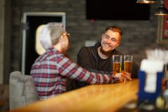 A happy guy, sitting and talking in a bar with a girl, drinking beer and laughing. Indoors. stock photography