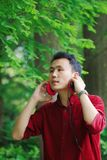 Happy careless free Asian Chinese man is listening to music and wearing a earphone. Happy handsome careless free Asian Chinese man in red shirt is listening to royalty free stock photography