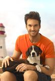 Happy handsome casual guy with dog laying in lap Royalty Free Stock Images