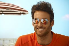 Happy handsome casual man wearing mirror shades. Happy handsome casual caucasian bristly men on holiday beach wearing mirror shades, outdoor. Smiling, girlfriend Royalty Free Stock Photos