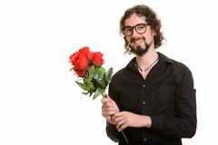 Happy handsome Caucasian man holding red roses ready for Valenti. Ne`s day royalty free stock photography