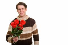 Happy handsome Caucasian man holding red roses ready for Valenti. Ne`s day royalty free stock photo