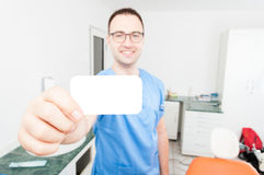 Happy handsome dentist showing business card Stock Photos