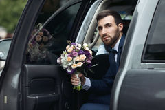 Happy handsome groom with a beard, getting out of wedding car ho Royalty Free Stock Image