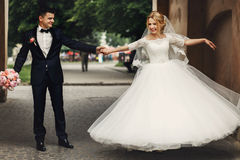 Happy handsome groom and blonde beautiful bride in white dress d. Ancing under arc Stock Photos
