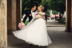 Happy handsome groom and blonde beautiful bride in white dress d. Ancing under arc Stock Images
