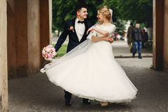 Happy handsome groom and blonde beautiful bride in white dress d. Ancing under arc Royalty Free Stock Photo